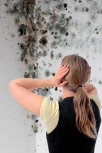 Blonde Frau mit Zopf steht bestürzt vor einer Zimmerecke, die mit Schimmel befallen ist.