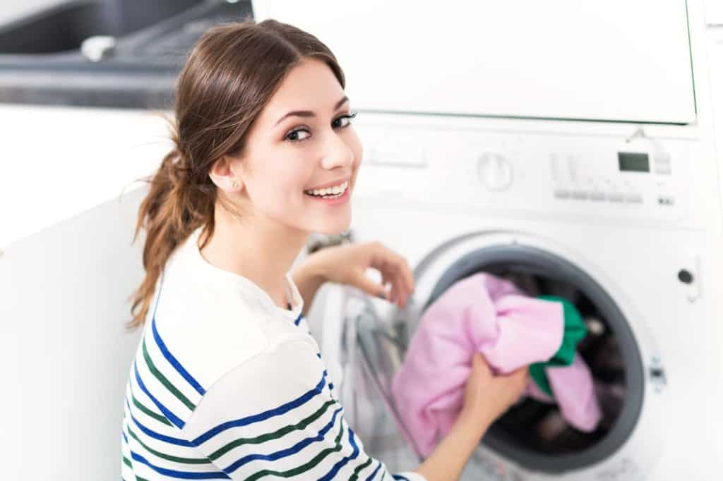 Woman loading washing machine – Warmwasser sparen