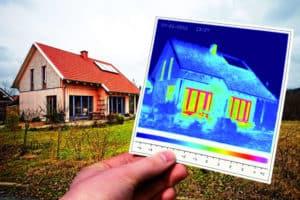 Vor einem Haus hält eine Hand das Bild einer Wärmebild-Kamera hoch.