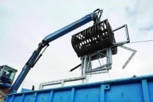 Nach dem Fensteraustausch: Ein Bagger hebt mehrere alte Fensterprofile in einen blauen Container.