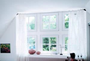 Nach dem Fensteraustausch ist vor der Pflege: Mehrere kleinere weiße Kunststoff-Fenster, die in den Garten hinaus führen, umrahmt von weißen Gardienen.