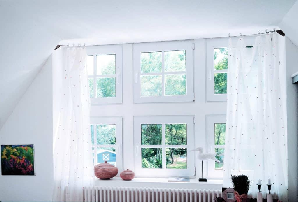 Nach dem Fensteraustausch ist vor der Pflege: Mehrere kleinere weiße Kunststoff-Fenster, die in den Garten hinaus führen, umrahmt von weißen Gardinen.