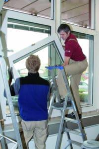 Fachkräfte im Einsatz: Zwei Männer tauschen ein Fenster aus.