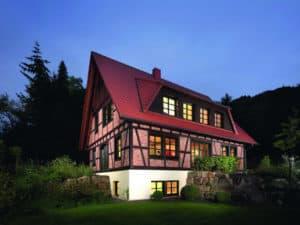 Ein Fachwerkhaus: rotes Dach und farbige Fensterprofile.