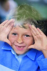 Mehr Wohnkomfort durch gute Fensterprofile. Ein kleiner Junge mit Sommersprossen drückt seine Nase gegen eine Fensterscheibe.