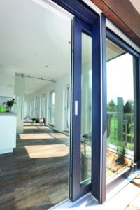 Mehrfarbige Fensterprofile an einem Wohnhaus: Außen dunkelbraun und innen weiß.