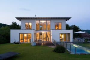 Wärmeverluste nein danke: ein modernes weißtes Flachdachhaus mit hell erleuchteten, großflächigen Fenstern.