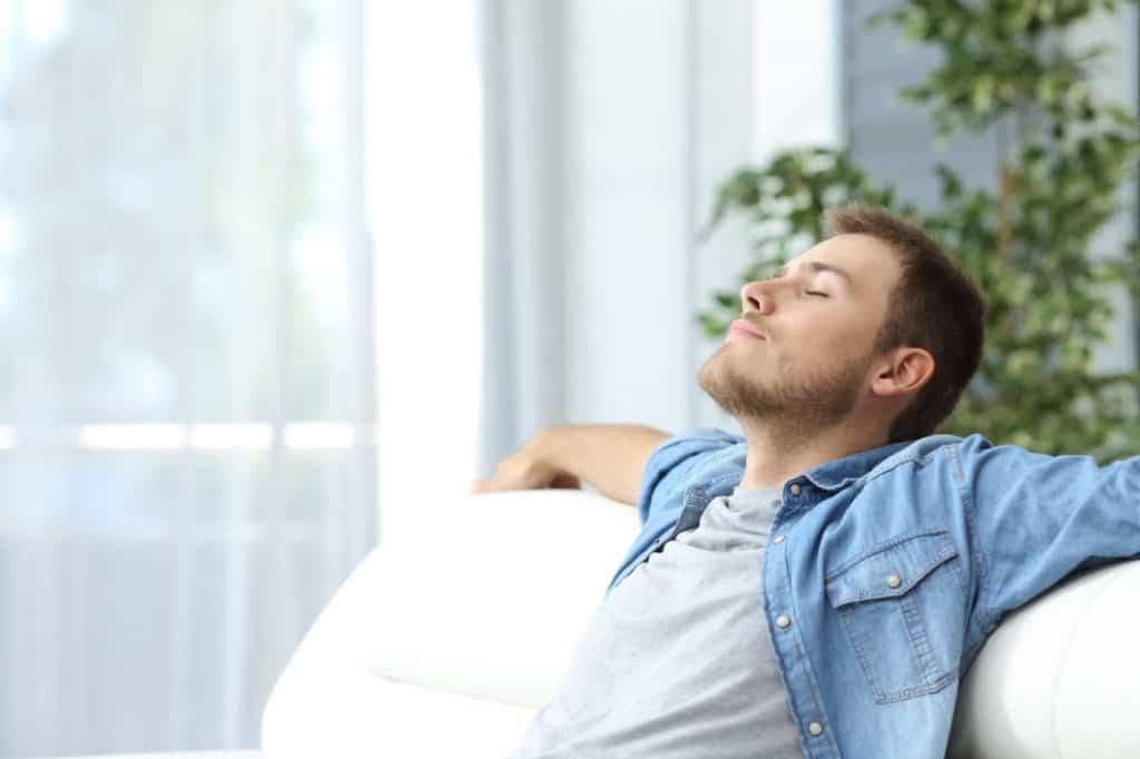 Junger Mann lehnt sich entspannt auf einem Sofa zurück – Allein reisen