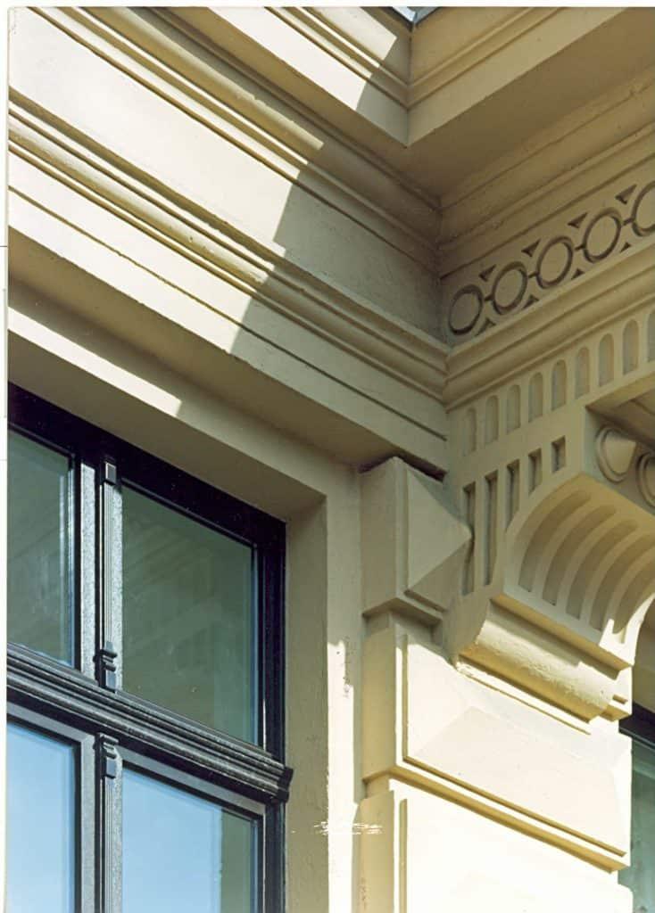 Fensteraustausch trotz Denkmalschutz: Nahaufnahme eines archtektonisch verzierten Gebäudes mit Fenster.