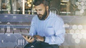 Vernetzt: Mann mit Bart und blauem Hemd bedient ein Tablet.