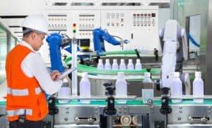 Die Produktion läuft: Ein Mann mit oranger Sicherheitswester überprüft die Funktionstüchtigkeit einer Maschine.