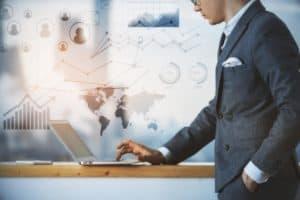 Kein Mangel an Informationen: Mann im Anzug und mit Brille steht neben einem Laptop und informiert sich im Internet.