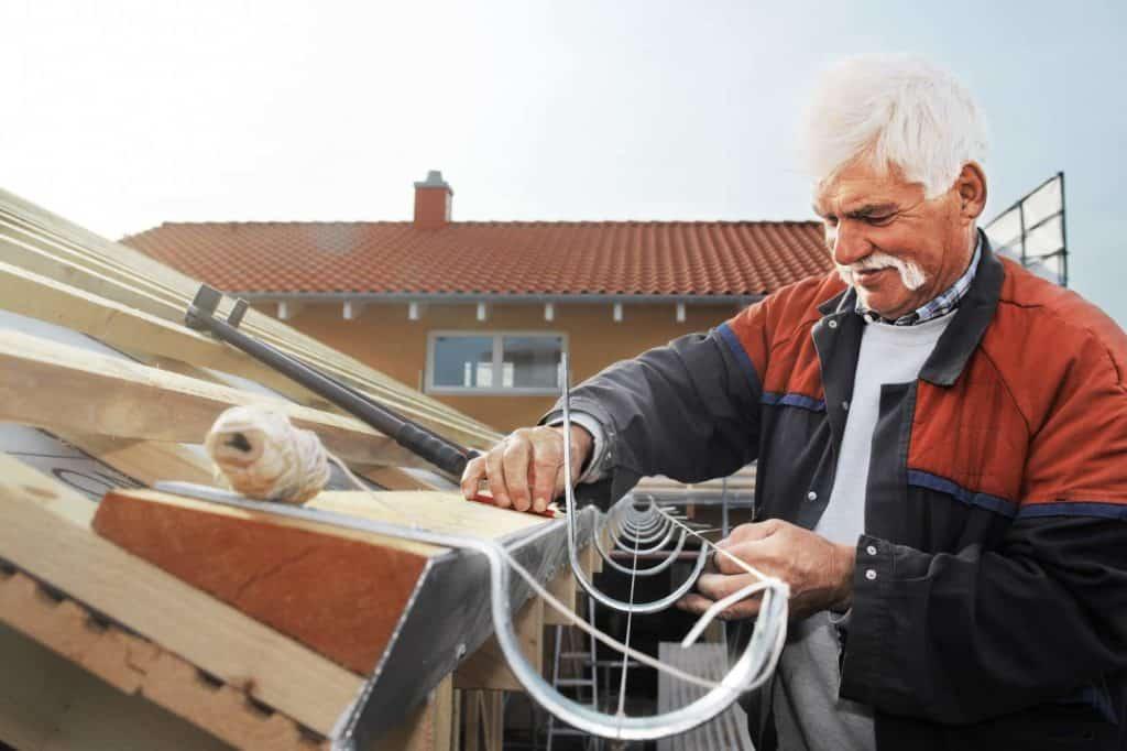 Ein Klempner mit Schnurbart montiert auf einem Dach eine Regenrinne