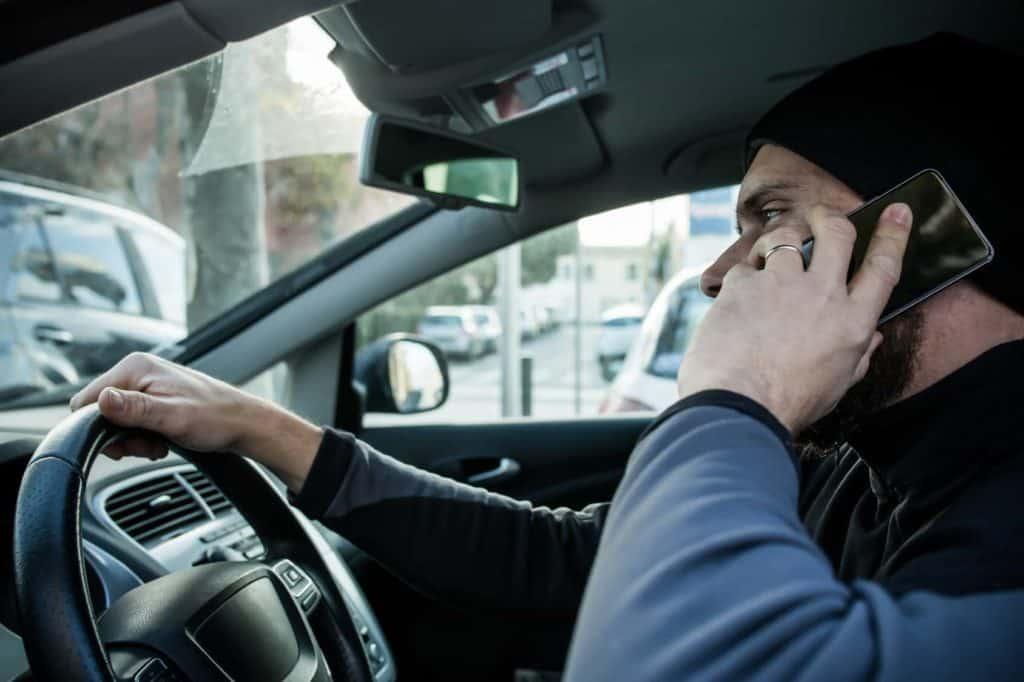 Urlaub mit dem eigenen Auto: Man mit Mütze und Bart am Steuer mit Handy.