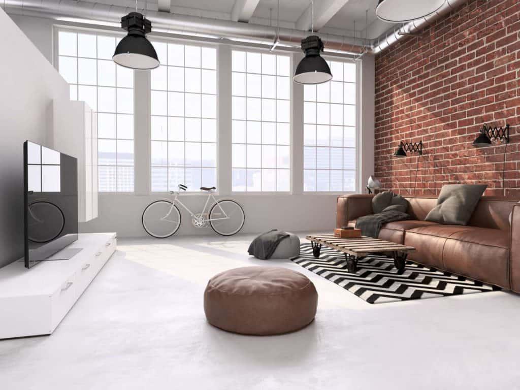 Moderne Möbel im Kontrast zur Backsteinwand, rustikalen Ledermöbeln und einer unbehandelten Holzpalette. Im Hintergrund Fahrrad vor einer Fensterfront im Loft.