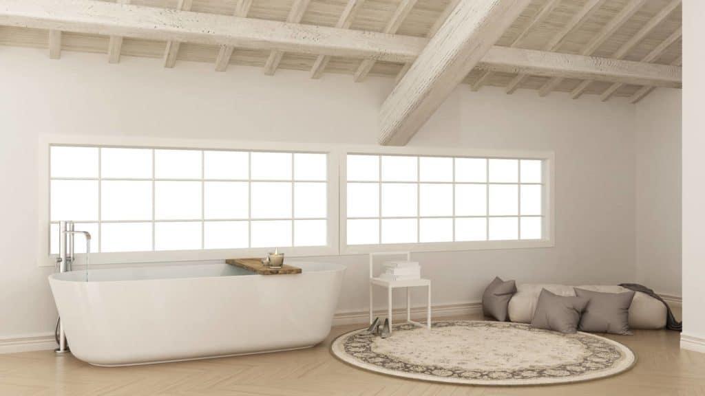 Freistehende Badewanne im Loft neben rundem Teppich und Kissen.