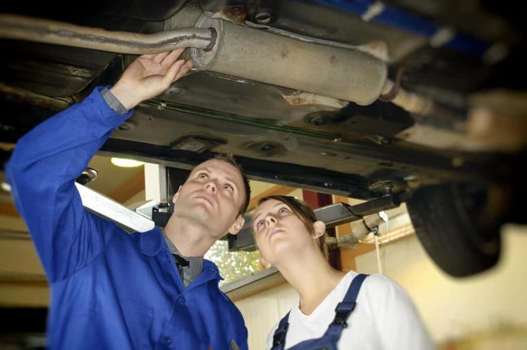 Mädchen im Männerberuf – na und?: KFZ-Meister zeigt der jugendlichen Auszubildenden die Prüfung der Auspuffanlage am Unterboden in der Autowerkstatt.