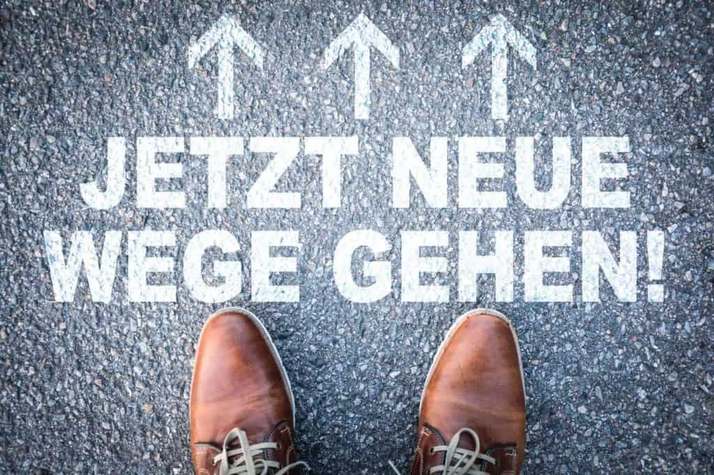 Schrift: Jetzt neue Wege gehen! und 2 Schuhspitzen (Thema: Den falschen Job angenommen)