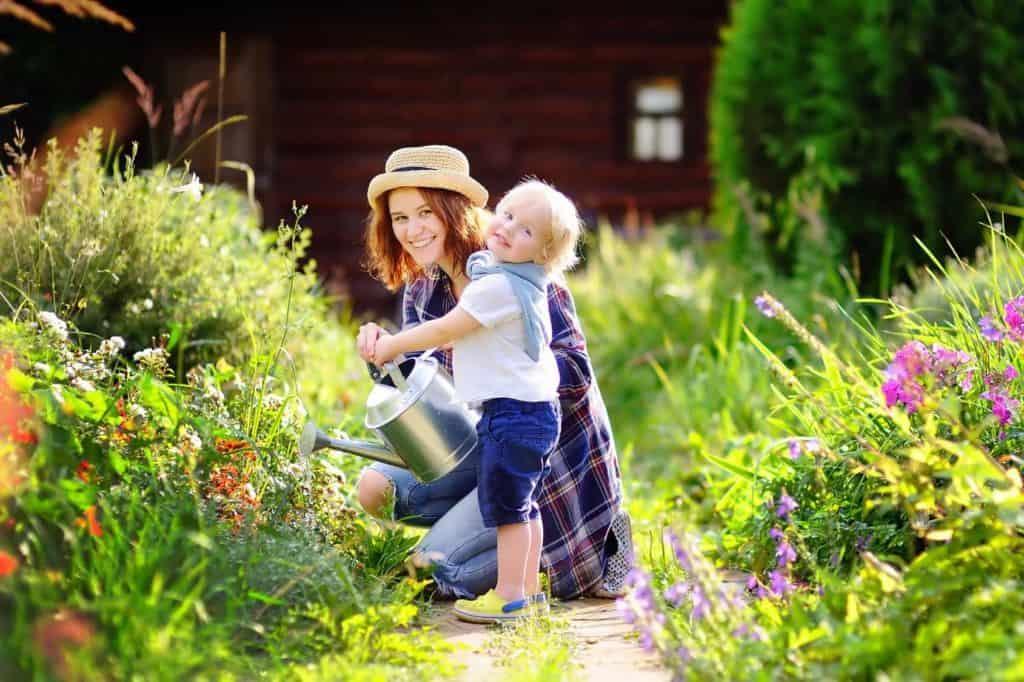 Cottage Gärten - kleines Kind gießt mit seiner Mutter Blumenstauden.