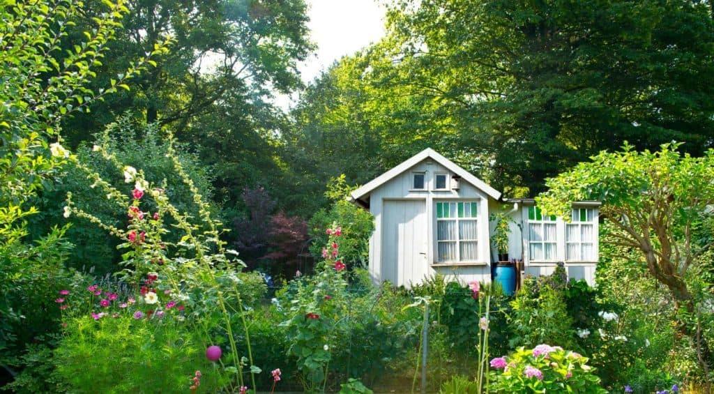 Kleines weißes Gartenhaus zwischen vielen Stauden – Cottage Gärten