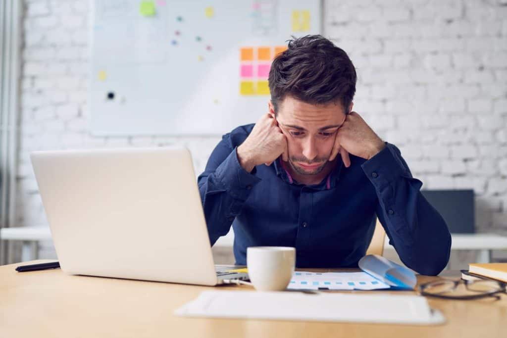 Den falschen Job angenommen: Depressiver Mann sieht auf die Unterlagen auf seinem Schreibtisch.