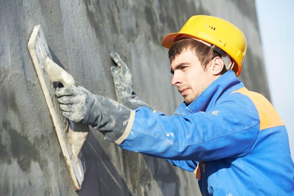 Ein junger Mann trägt Putz auf eine Hauswand auf.