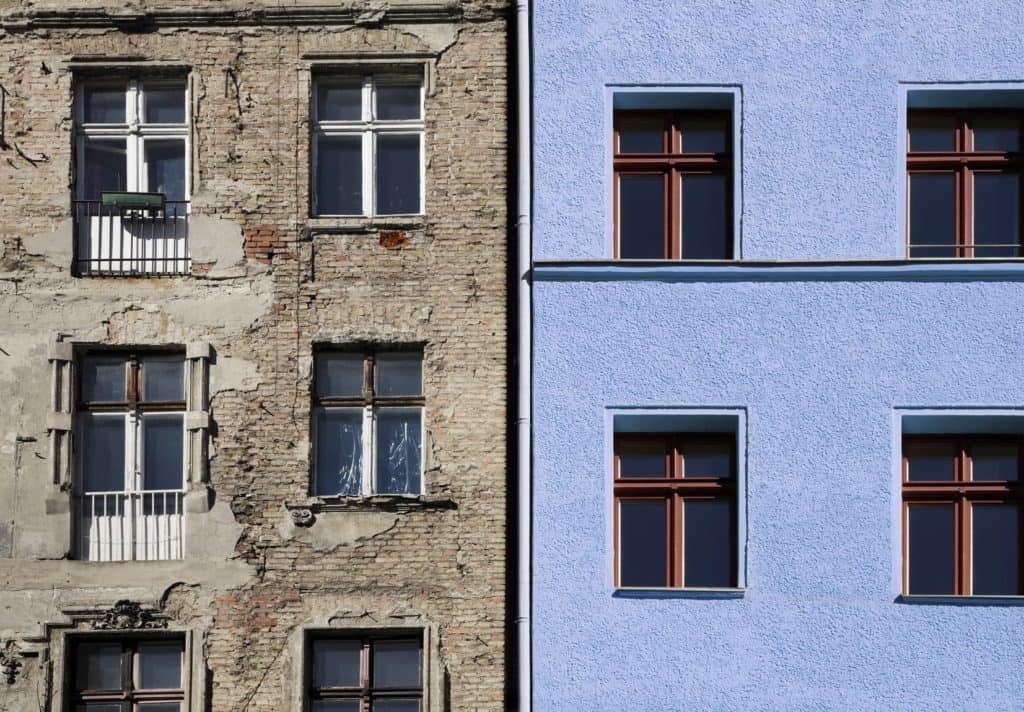 Eine sanierungsbedürftige Häuserfassade neben einer Fassade, die mit blauem Edelputz saniert wurde.