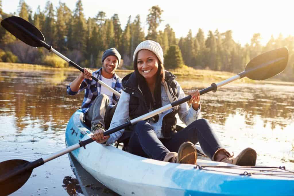Junges Paar auf einer Spontanreise auf dem Wasser im Kanu bei Herbstwetter.