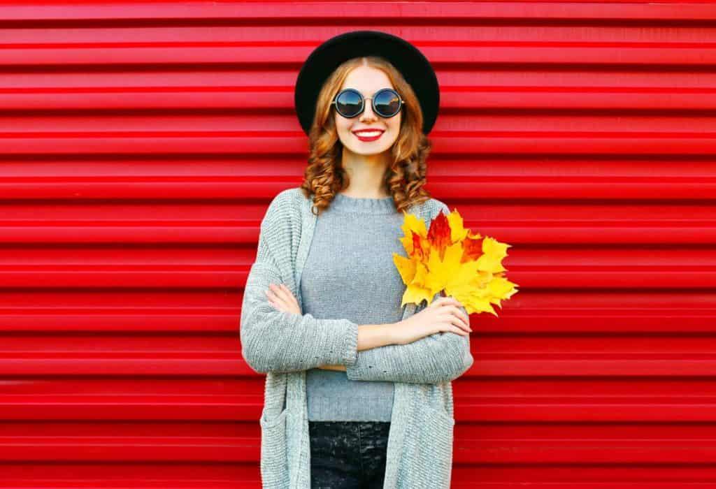 Junge Frau mit Sonnenbrille und Hut steht mit leuchtenden Ahornblättern in der Hand vor einem knallrotem Wellblech.