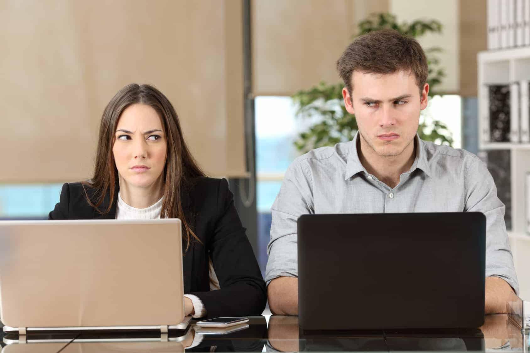 Mann und Frau sitzen vor ihren Laptops und werfen sich böse Blicke zu (nervige Kollegen)