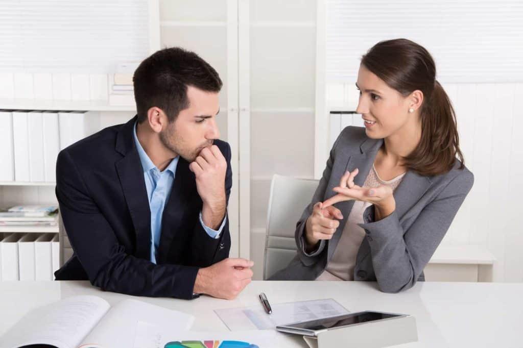 Junger Mann hört einer jungen Frau im Büro aufmerksam zu. (Nervige Kollegen)