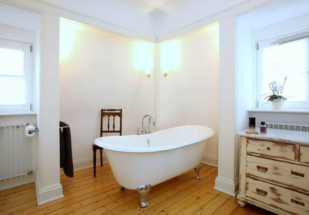 Wohnbad mit Holzfußboden, freistehender Badewanne, Kommode und Holzstuhl.