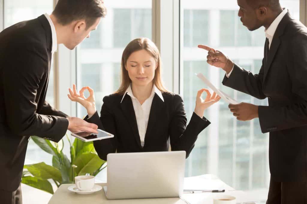 Während zwei nervige Kollegen im Büro stehend streiten, sitzt eine junge Frau dazwischen, schließt die Augen.