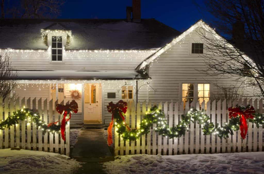 Dezente, leuchtende Weihnachtdeko am Haus und Gartenzaun.