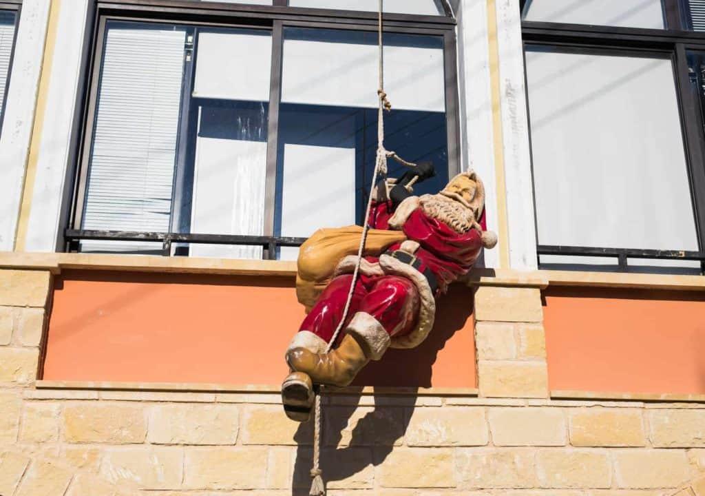 Weihnachtsdeko am Haus: Weihnachtsmann-Puppe an der Fassade