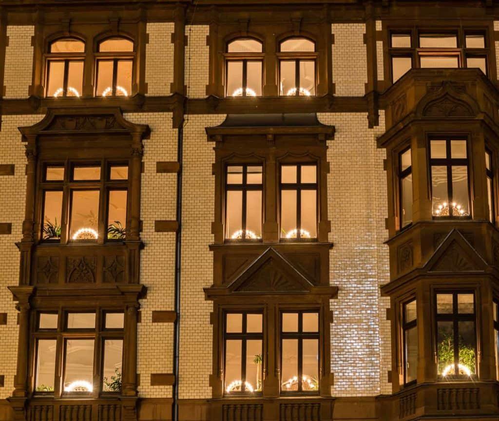 viele Lichterbögen in den Fenstern eines Mietshauses (Weihnachtsdeko am Haus)