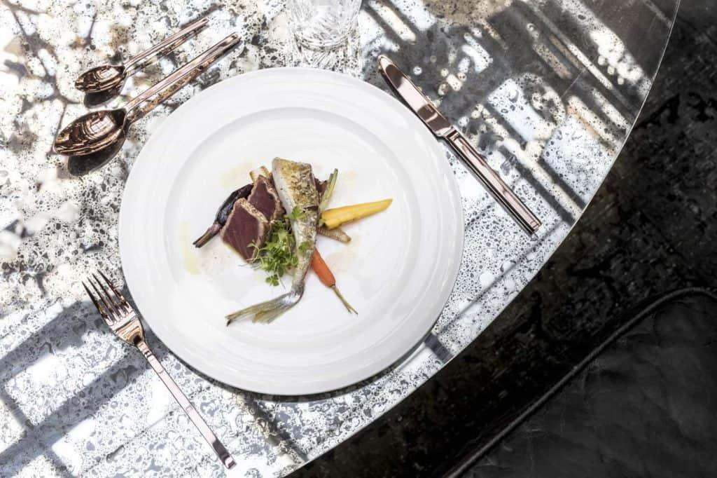 Teller mit Fischgericht und daneben Kupferbesteck auf einer Tischplatte. (edle Geschenke)