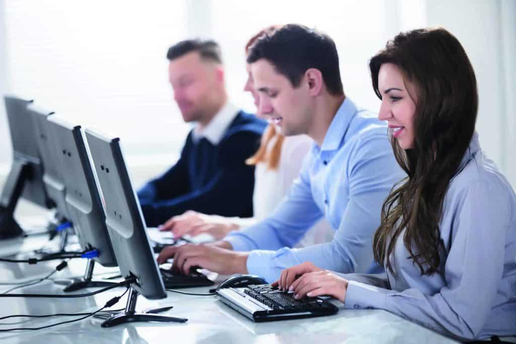 E-Commerce-Kaufmann: Manner und Frauen sitzen vor dem PC und arbeiten.