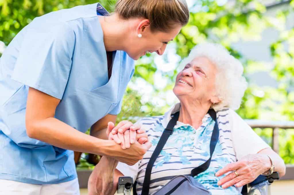 Krankenschwester hält die Hand einer alten Dame im Rollstuhl. (Zukunftsberufe)