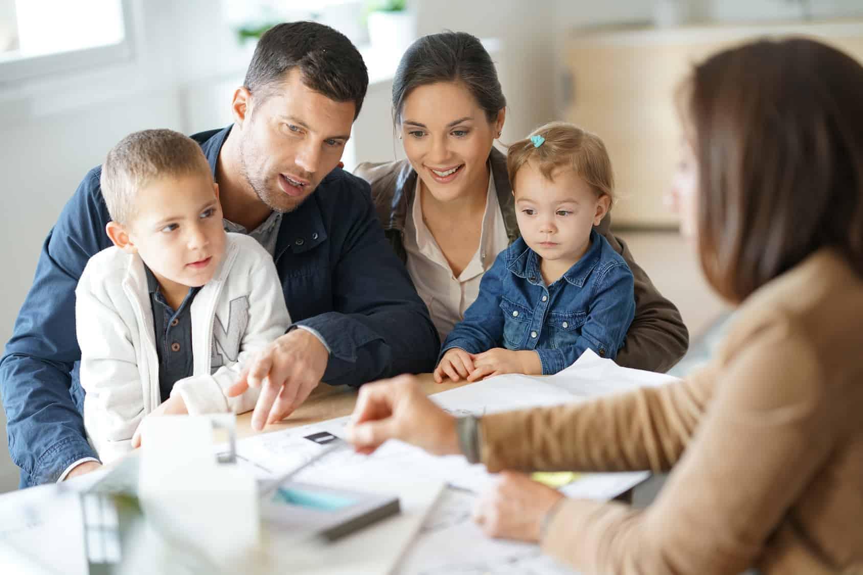 Junges Paar mit zwei Kinder bespricht mit Architektin die Baupläne. (Schutz für Baufamilien)