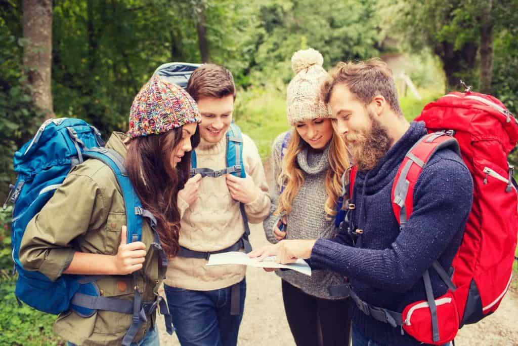 Eine Gruppe fröhlicher, junger Leute beim Blick auf die Wanderkarte (Wandertipps für Anfänger)