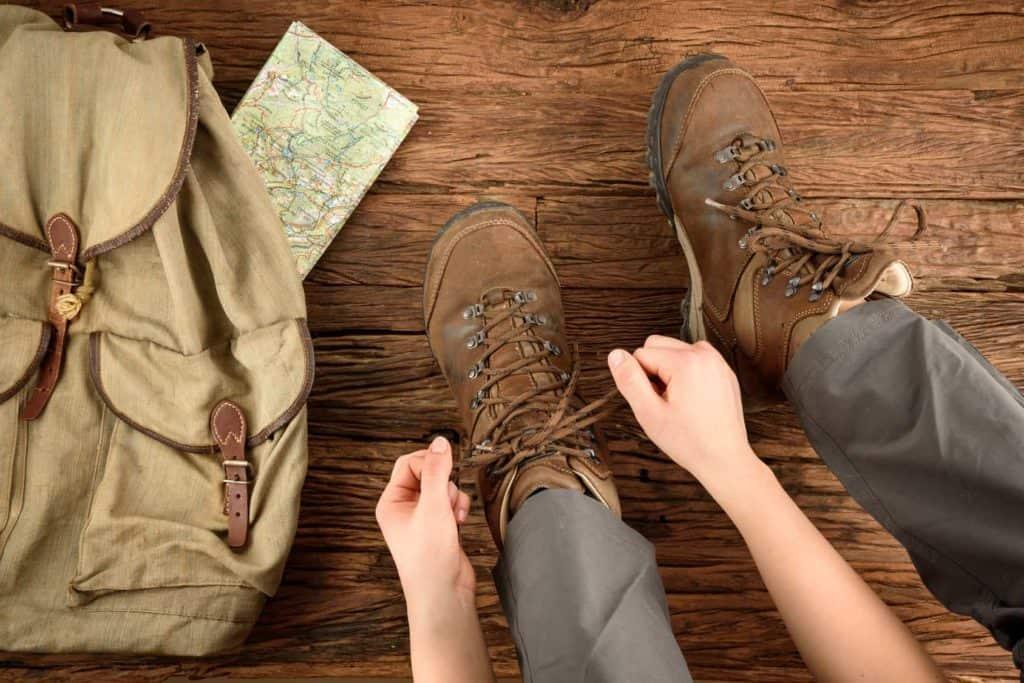 Rucksack, Wanderkarte und Wanderschuhe, die geschnürt werden (Wandertipps für Anfänger)