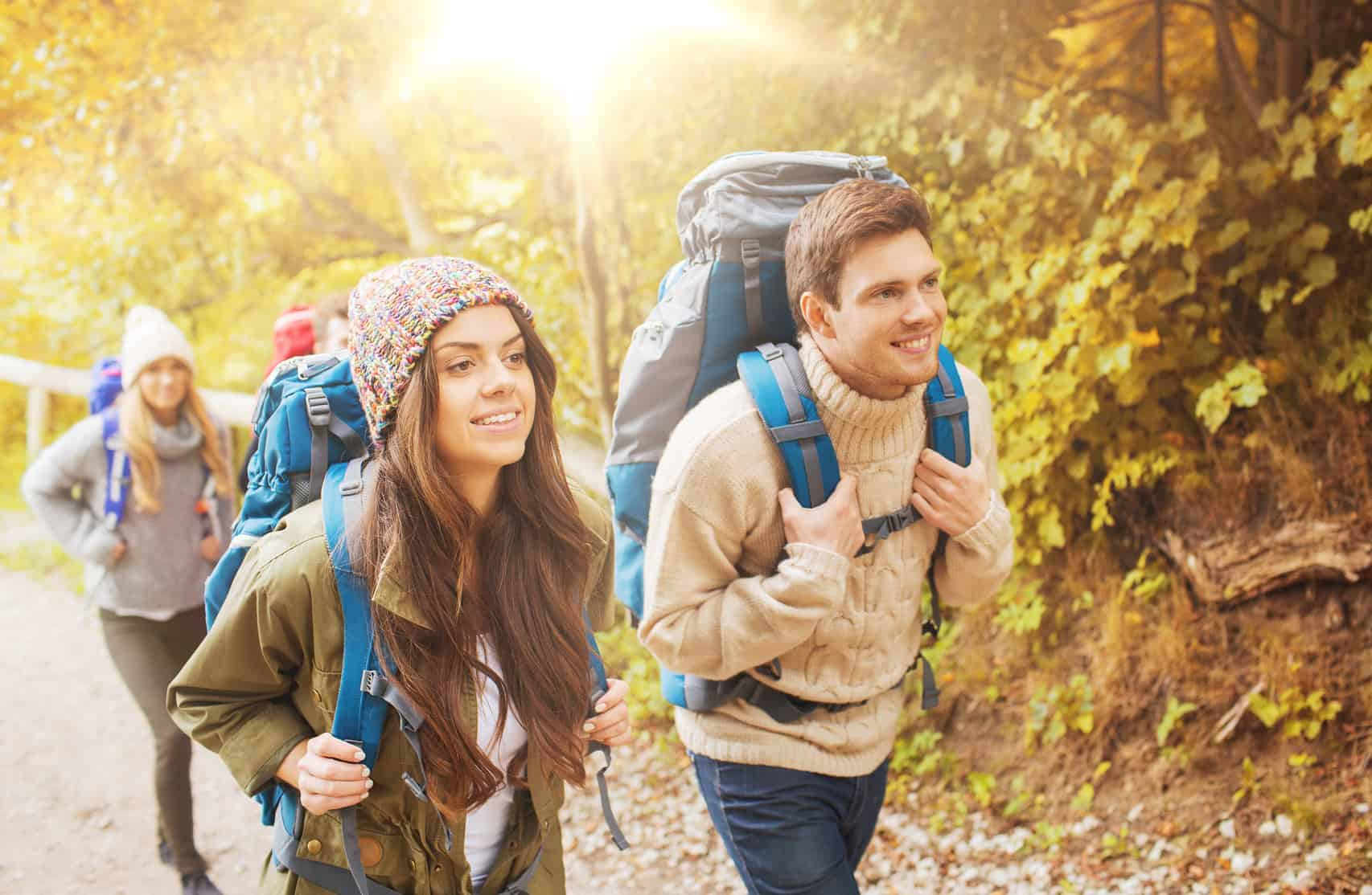 Junge Leute beim Wandern mit Rucksack durch den Wald. (Wandertipps für Anfänger)