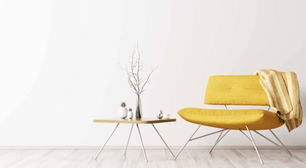 Sessel, Beistelltisch mit wenigen Deko-Elementen vor weißer wand (Gemütlich minimalistisch wohnen)