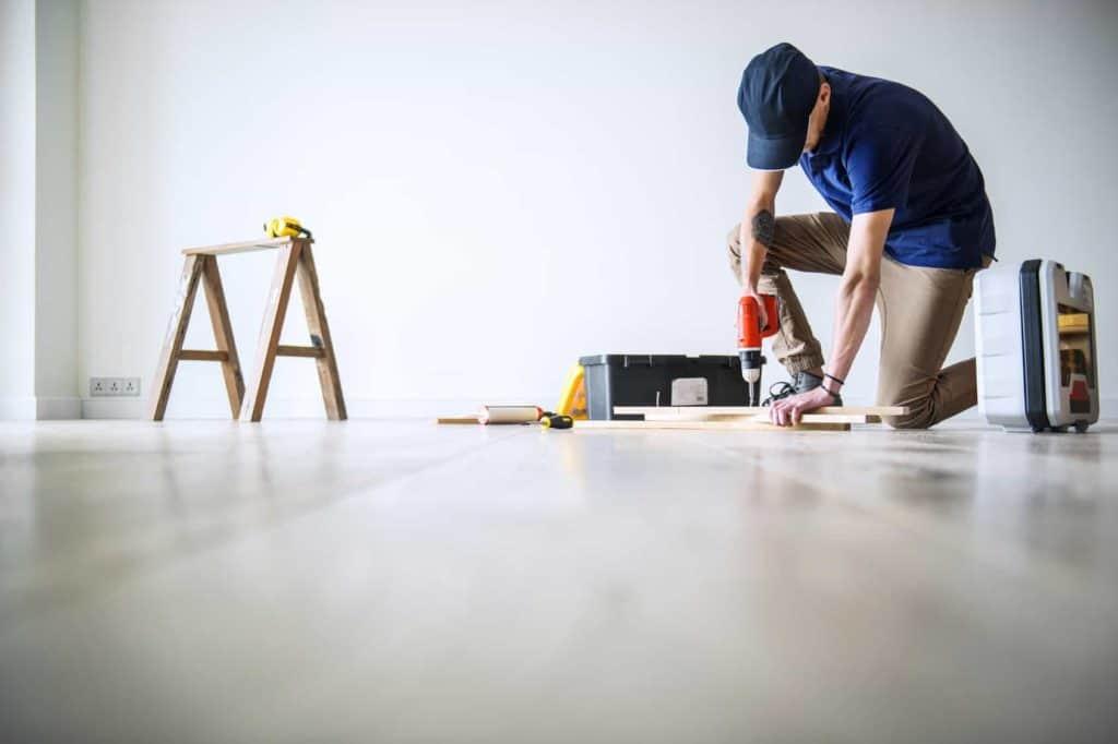 Mann bohrt beim renovieren seiner Wohnung in ein Brett. (laute Nachbarn)