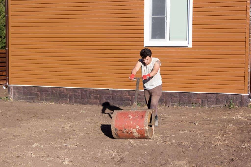 Mann walzt mit einer Handwalze (Wildblumenwiesen im Garten)