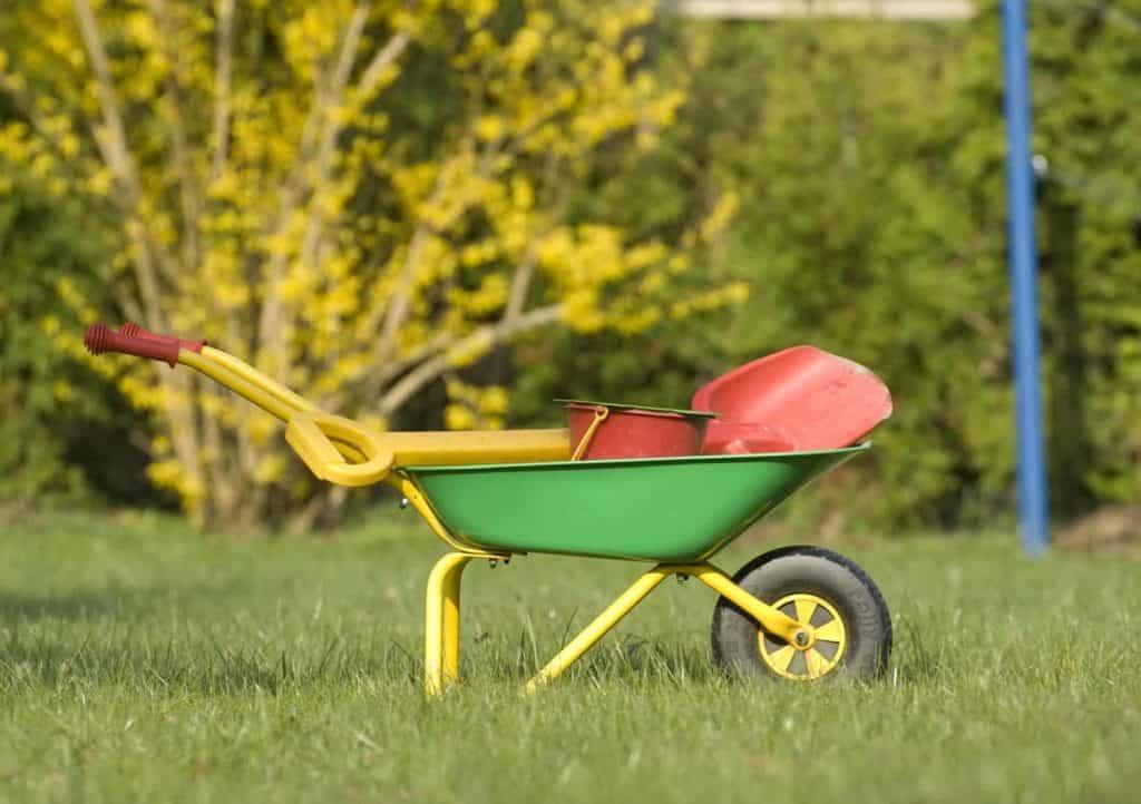 Kinderschubkarre, Kinderschaufel, kleiner Eimer auf einer Rasenfläche (Kinderbeet)