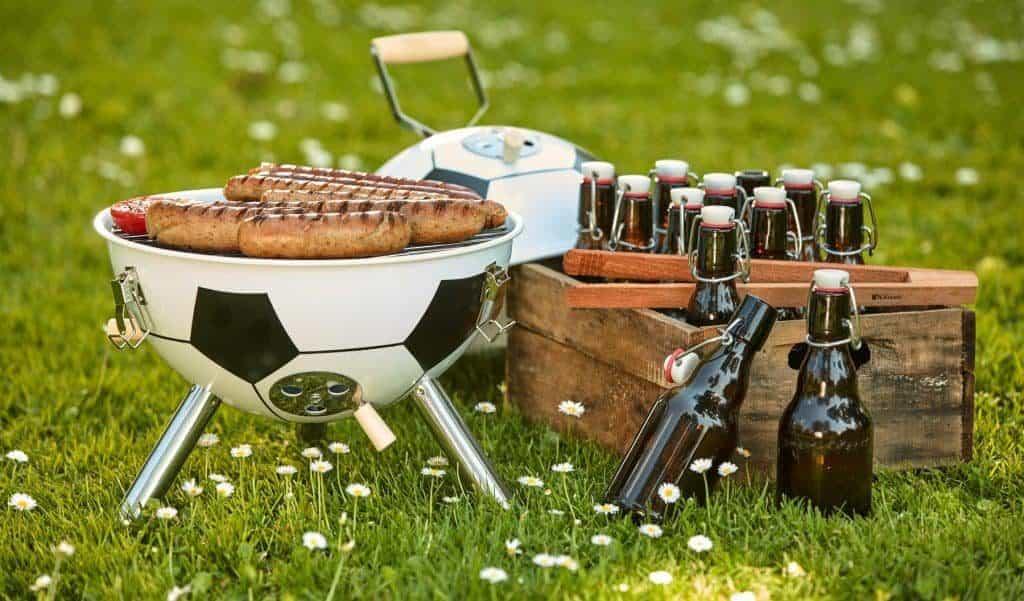 Kleiner Fußballgrill mit Würstchen und Bier auf dem Rasen (So gelingt die WM-Party im Garten)