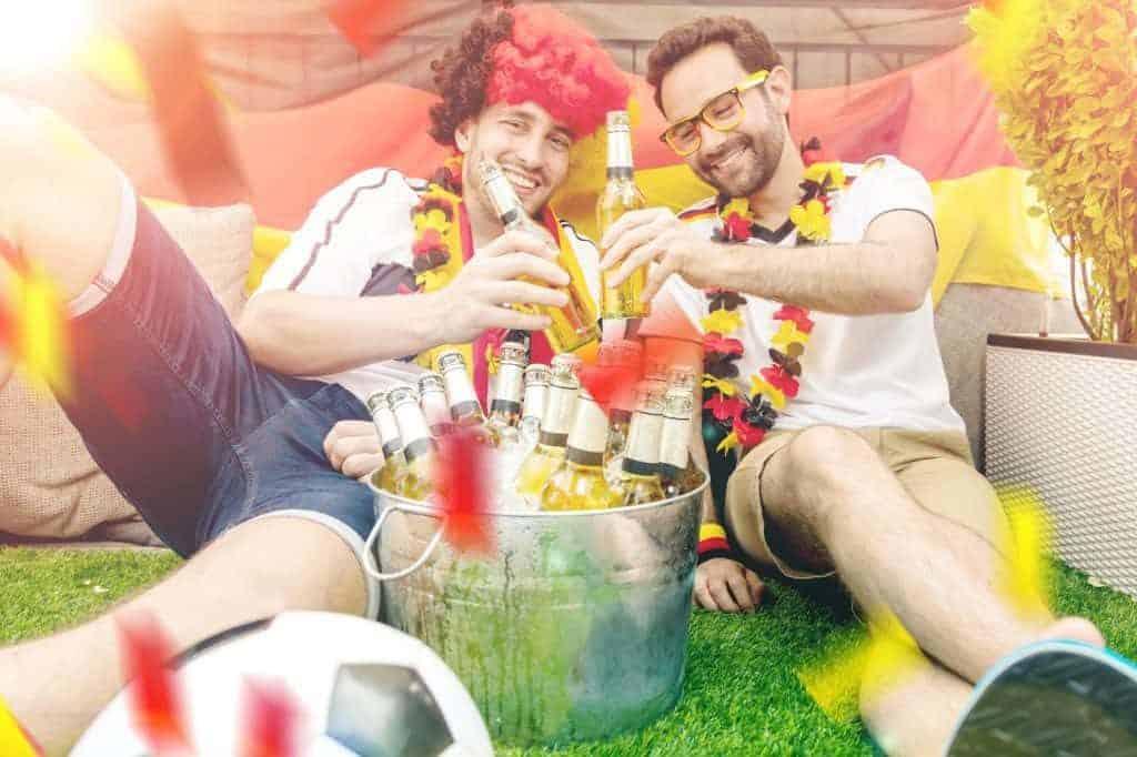 Zwei Männer in Fanbekleidung sitzen auf dem Rasen vor einem Eimer mit gekühlten Bierflaschen (WM-Party im Garten)