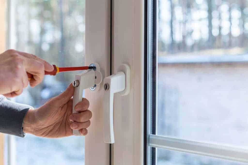 Hände schrauben mit einem Schraubenzieher am Fenstergriff. (Fensterplanung)